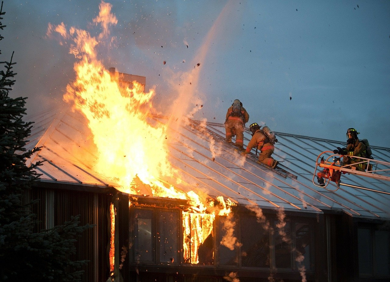 firefighters on roof of structure on fire