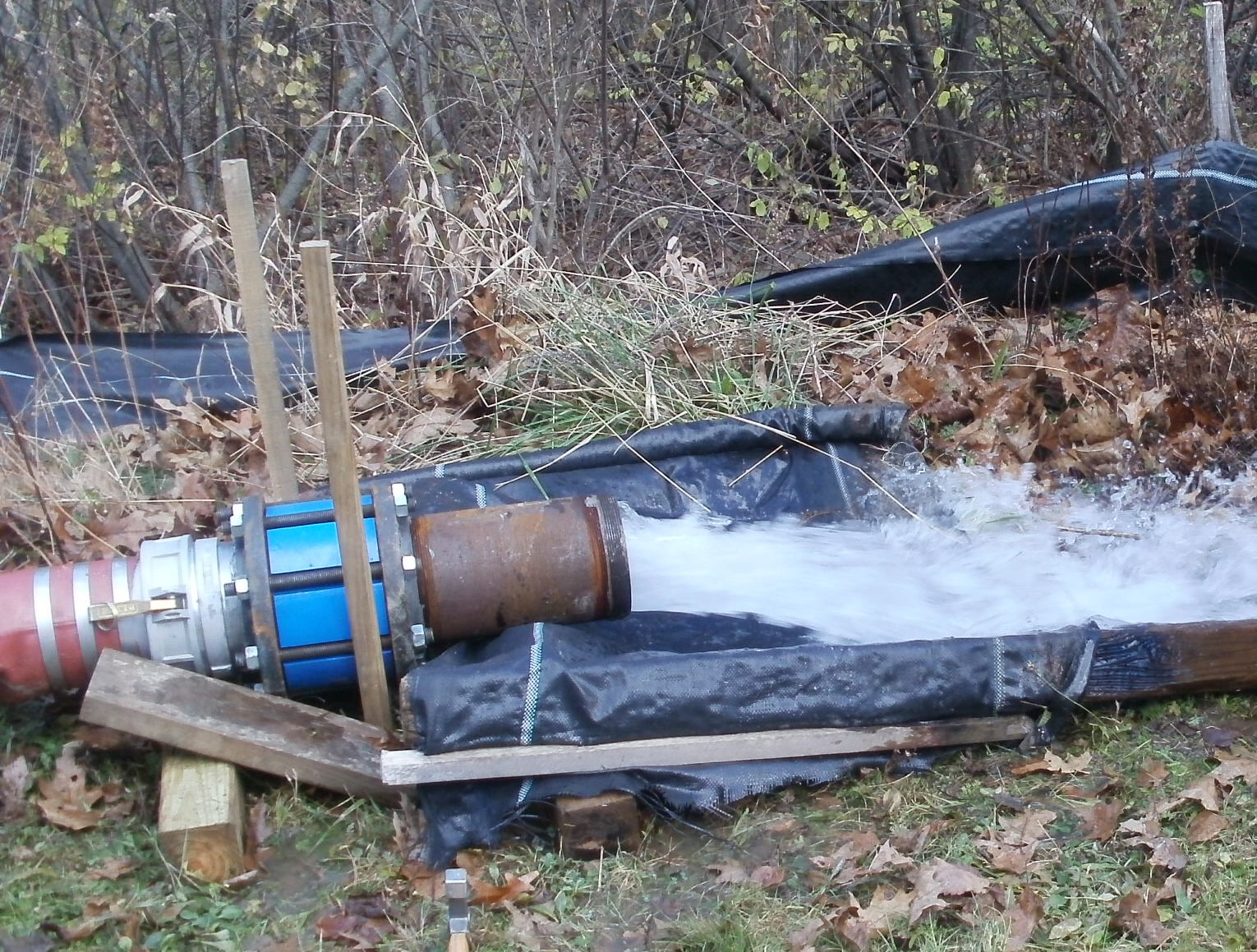 large diameter pipe on the ground with water gushing out of it