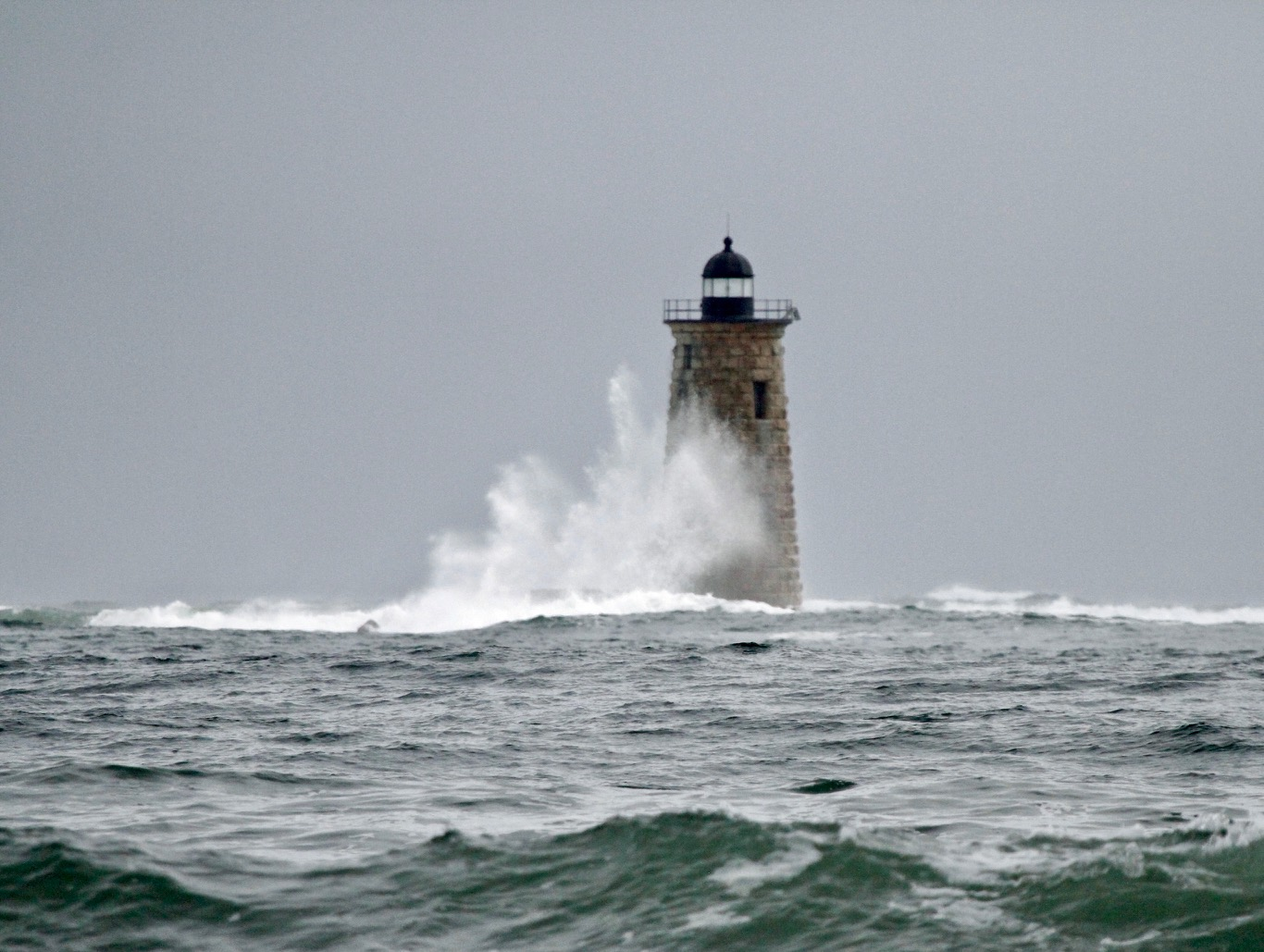 a wave breaks on the edge of a lighthouse
