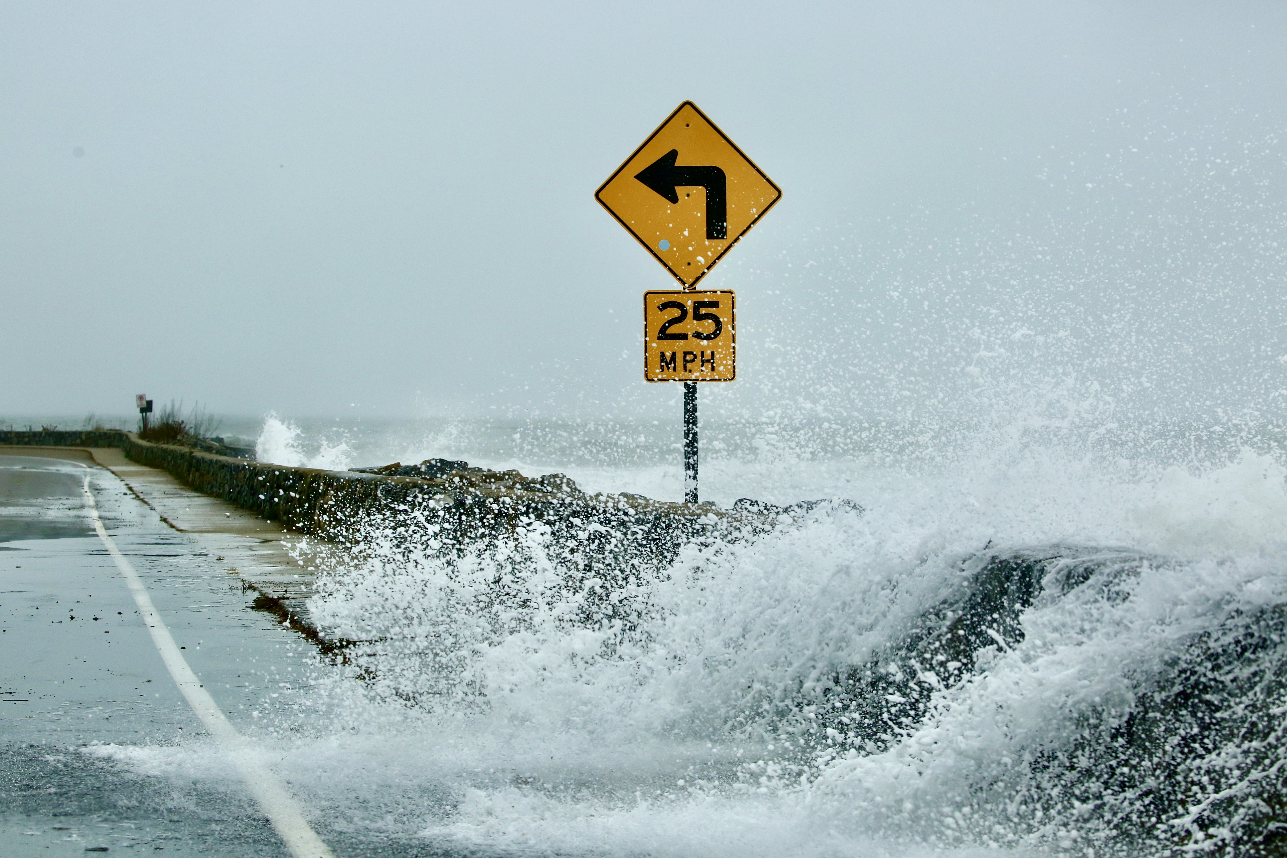 a wave breaks over a seawall and into a roadway.