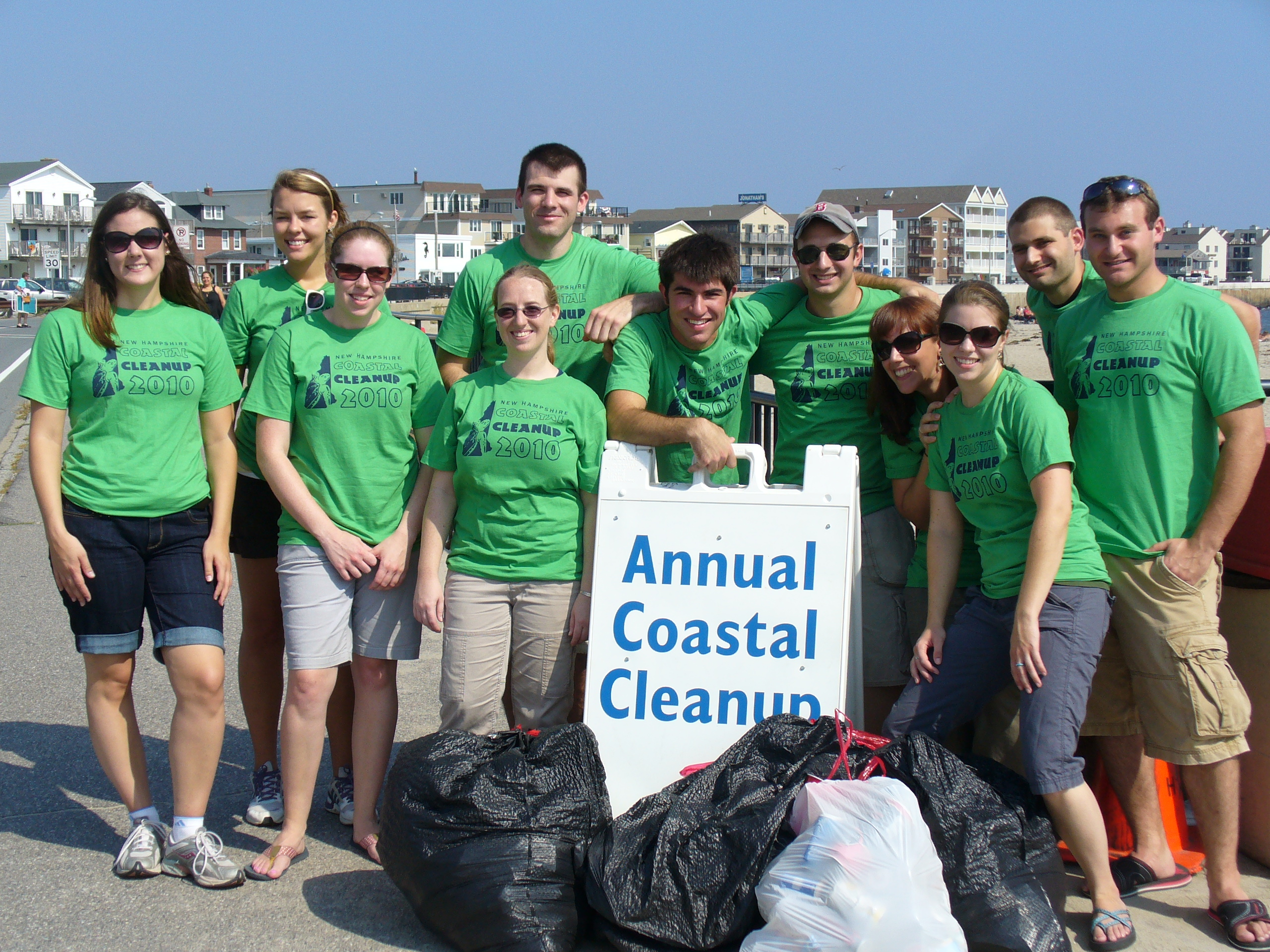 group of volunteers with full trash bags and an Annual Coastal Cleanup sign in front of them.