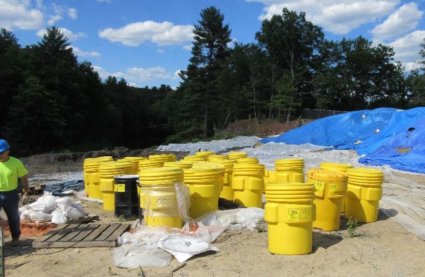 drums and tarps covering soil piles