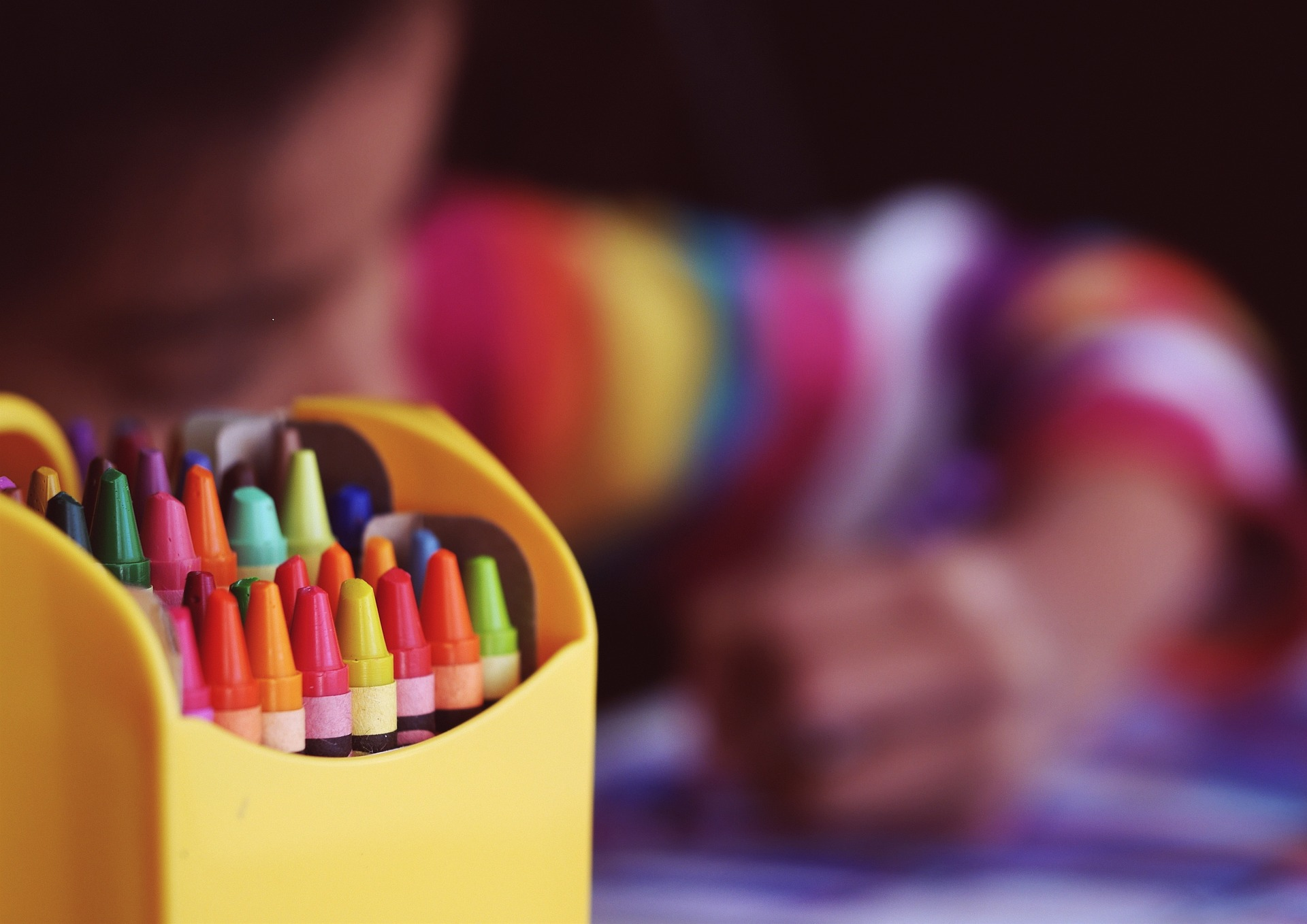 image of crayons with blurred image of child coloring in background