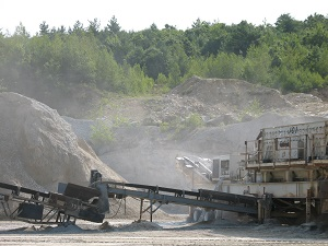 Dust fills the air around a rock crushing operation.