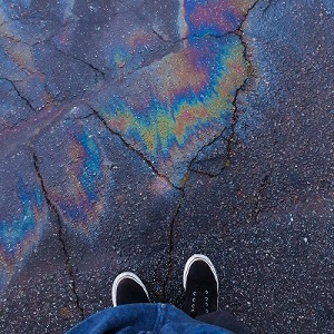 A person stands in front of an oil slick on pavement