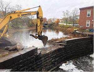 An image of heavy equipment removing a dam