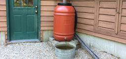 a rain barrel is situated next to a house